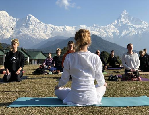 People sitting in front of Himalayas during Meditation teacher training