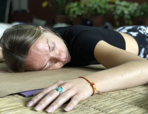 A woman sleeping in belly on Yoga mat in Yoga Nidra Training