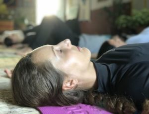 A head of a girl in savasana with closed eyes