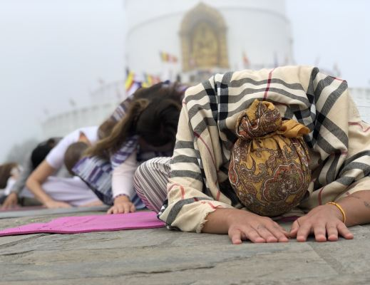 women doing child pose in front of Peace pagoda during her 300 hour Yoga training in Nepal