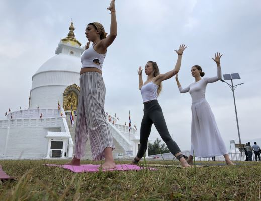 Ladies doing Standing yoga pose at Peace stupa during holistic 200 hours Yoga teacher training course in Himalayas