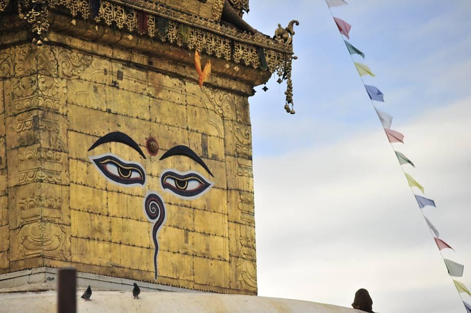 Chanting peace Mantra looking at Buddha eyes on temple wall